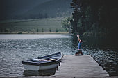 Man kneeling praying surrendering on a wooden jetty on a beautiful lake with a moored rowboat in nature