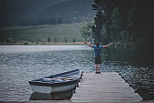 Man with arms raised outstretched standing legs together on a wooden jetty on a beautiful lake with a moored rowboat in nature