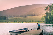 Man kneeling hands clasped together praying on a wooden jetty on a beautiful lake with a moored rowboat at sunset