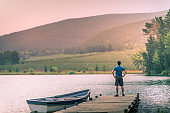 Man hand on hip standing on a wooden jetty on a beautiful lake with a moored rowboat at sunset