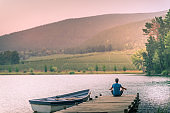 Man meditating on a wooden jetty on a beautiful lake with a moored rowboat at sunset