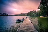 A mid adult Man sitting looking on a wooden jetty in a beautiful lake with a moored rowboat dramatic sky