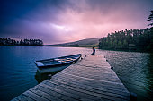 Wide shot of a mid adult Man on a wooden jetty kneeling praying in a beautiful lake with a moored rowboat dramatic sky