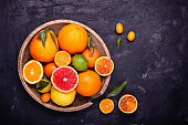 in the old wooden plate, various types of whole citrus fruits and others sliced.
