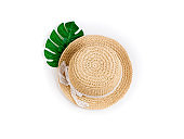 Summer background with straw hat and tropical palm leaf monstera. Female summer accessories. Summer, outfit, fashion, vacations, travel