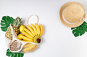 Summer female trendy fashionable composition. Straw hat, eco bag with tropical fruits on white background. Shopping, zero waste, vocations, fashion, travel concept. Flat lay, top view