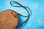 Fashionable natural round rattan bag on blue background flat lay. Trendy bamboo bag from Bali. Summer fashion concept