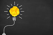 Idea Concepts Light Bulb Crumpled Yellow Paper on Chalkboard Background