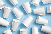 White disposable cups on the light blue background