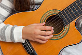 Hand of a little girl learning to play the guitar at her home