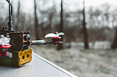 A small self made FPV drone lies on the table before the flight.