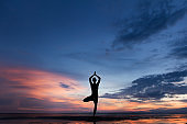 Silhouette photo of man practicing yoga at sunset