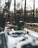 FPV drone lies on the table near the laptop and control panel.