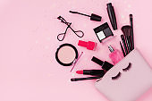 Woman makeup background with beauty products and cosmetics. Top view on pink table and flat lay.