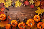 Autumn Thanksgiving background. Pumpkins, acorns and leaves on wooden table top view.