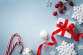Christmas flat lay. Gift or present box, white snowflakes and holiday decoration top view. Happy New Year card.