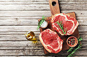 Fresh meat on wooden cutting board top view. Raw beef steak and spices for cooking.