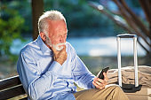 Bearded Senior man typing message in the park.