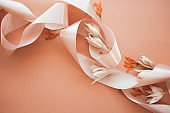 Feminine wedding desktop mockup with dry wildflowers and satin ribbon on coral background