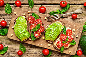 vegan sandwiches with avocado, tomatoes, basil, hummus and sesame seeds on rustic cutting board with fork