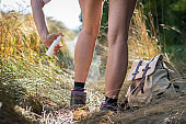Woman tourist applying insect repellent against tick and mosquito on her legs in nature