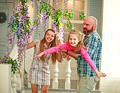 Happy parents with daughter have fun playing holding child on his hands, in courtyard summer family home