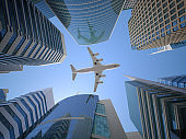 Airplane flying over skyscrapers n city downtown district. Business corporate travel background concept. 3