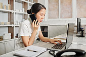 Receptionist checking schedule and answering phone call
