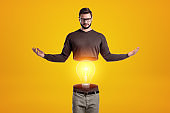 Man wearing glasses and casual clothes cut in half with light bulb inside on yellow background