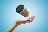 Female hand with coffee paper cup on blue background