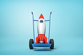 3d rendering of toy space rocket on blue hand truck which is standing in half-turn on light-blue background with copy space.