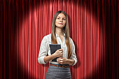 Front crop view of young attractive businesswoman holding daily planner standing in spotlight against red stage curtain.