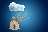 3d rendering of brown canvas money bag with dollar symbol, right under raining cloud on blue copy space background, the bag starting to break into pieces on top.