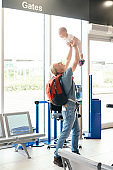 Young mother father with baby in duty free at airport