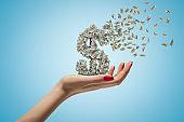 Female hand holding money dollar sign shattering on blue background