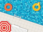 Swimming pool with swimming rings, umbrella and deck chair.