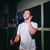 An expressive man sings a song in a microphone in a recording studio.