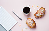 Coffee mug with croissants and empty notebook and pen for business plan and design ideas on pink background from above. Morning plan. Flat lay concept