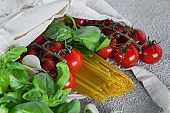 Reusable bag with groceries. Tote bag, minimal waste. Fresh basil, tomatoes cherry, garlic in fabric bag on dark table background. Top view, copy space.
