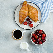 Delicious breakfast food concept. Coffee, croissants and berries for breakfast on light concrete background. Square image, top view