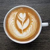 Top view of a mug of latte art coffee .