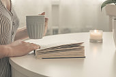 Close-up of female hands holding cup of tea or coffee in front of opened book. White table interior. Cozy Mood Home Concept