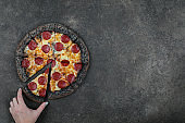 Female hand picking slice of pepperoni pizza with black dough. Tasty pepperoni pizza on dark concrete background. Top view of hot italian pizza. With copy space for text. Flat lay.