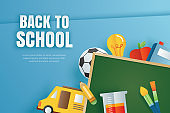 Back to school banner with education items on blue background in paper art style.