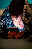 Boy hiding under duvet to play video games