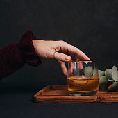 Woman drinking drink brandy whiskey or rum on ice