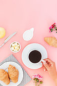 Morning breakfast coffee and croissant, butter, orange juice and flowers on white background. Flat lay, top view