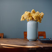 Vase with dried yellow flowers immortelle