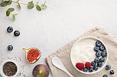 White fermented yogurt with blueberry, figs, chia seeds and raspberry in bowl on light gray table