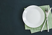Empty plate on dark stone background.